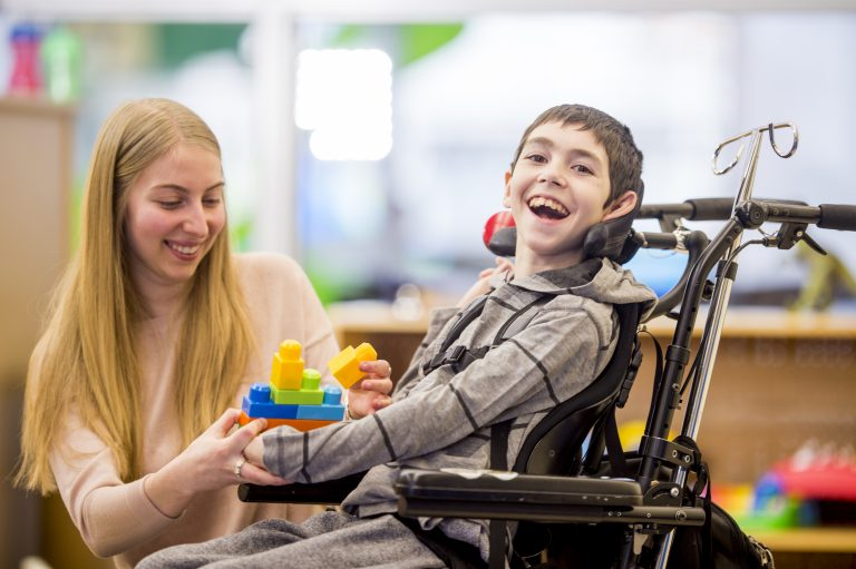 A caregiver is helping a young boy with a physical disability play with plastic block toys.