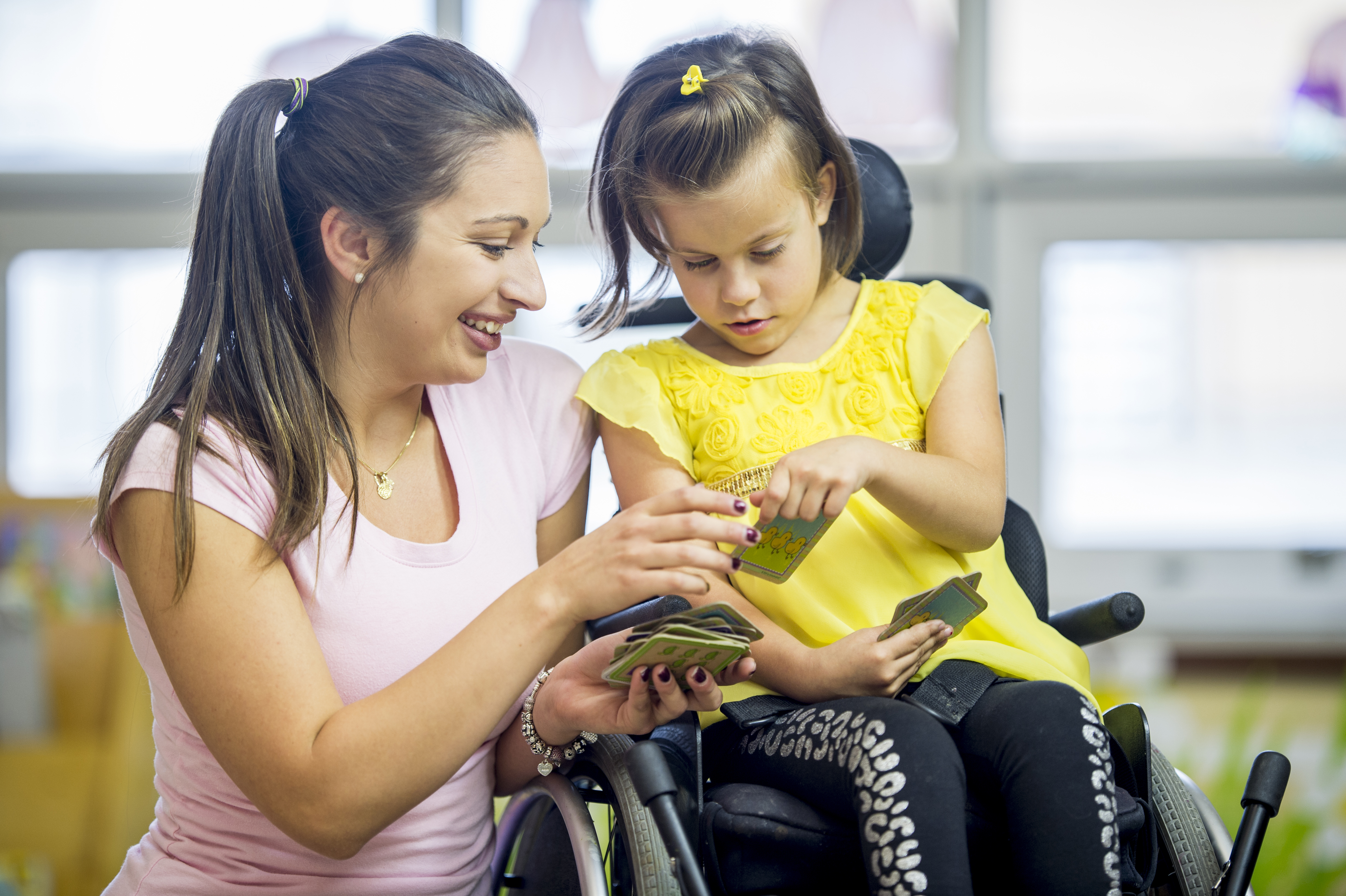 A Caucasian girl is sitting in her wheelchair inside a classroom. She is playing a card game with her educational assistant.